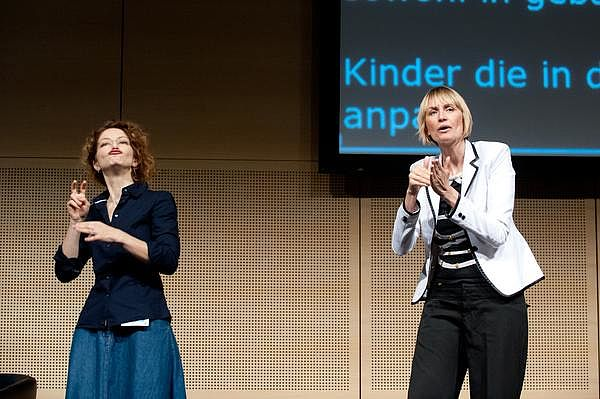 Vortrag auf dem Bildungskongress 2013 in Wien: Helene Jarmer (rechts im Bild) gebärdet ÖGS, eine Dolmetscherin übersetzt in International Sign Language.